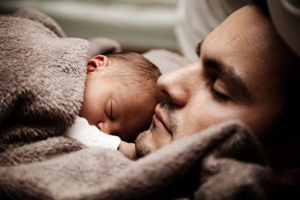 Father cuddling newborn