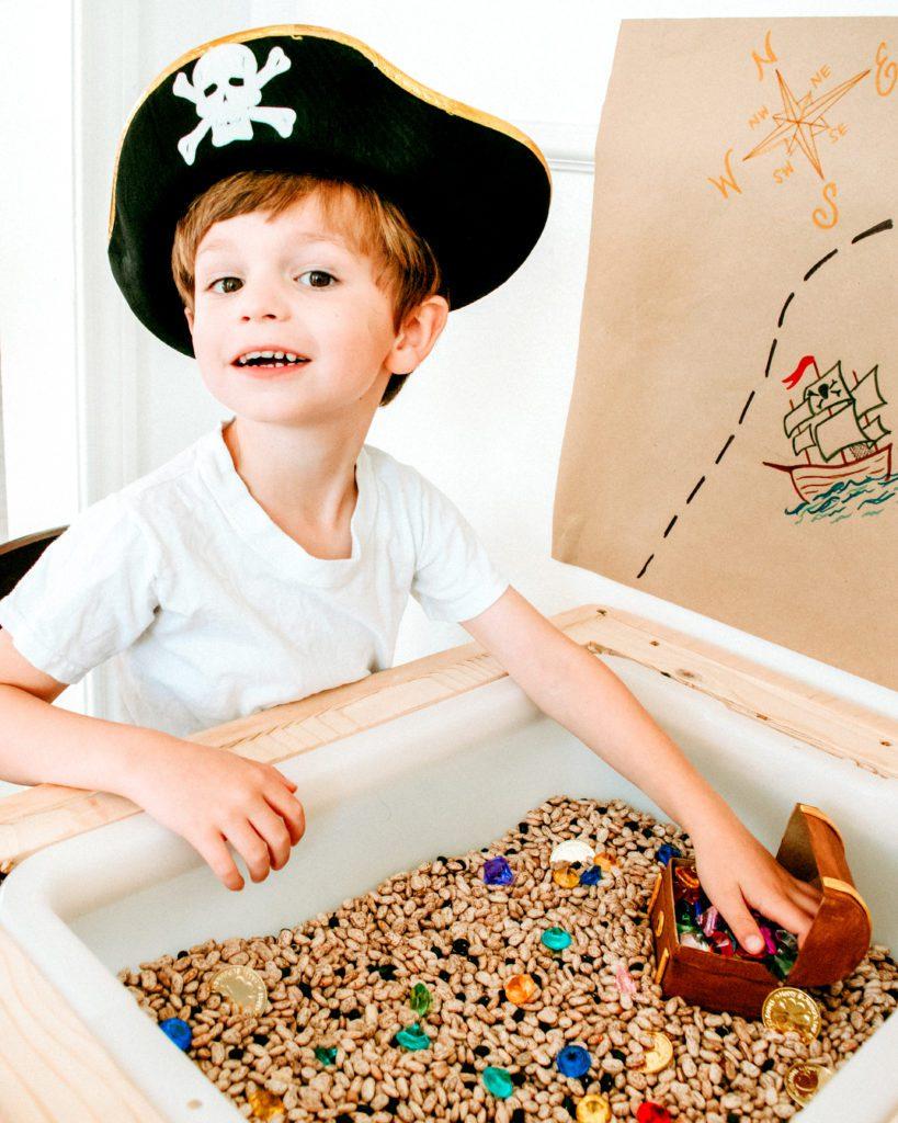 little boy playing in a sensory bin