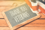 chalkboard by American flag with Thank You Veterans written on it