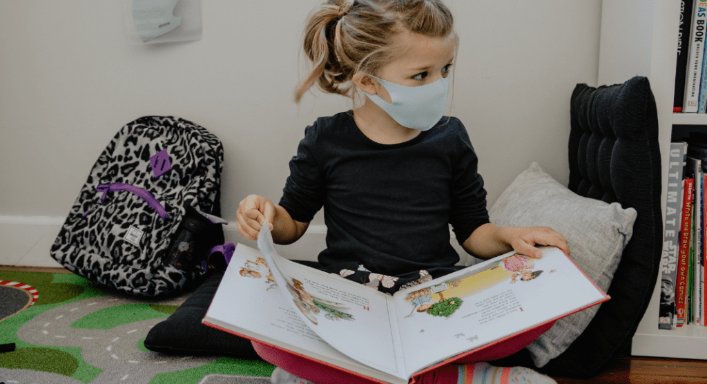 girl with mask reading a book for National Family Literacy Month