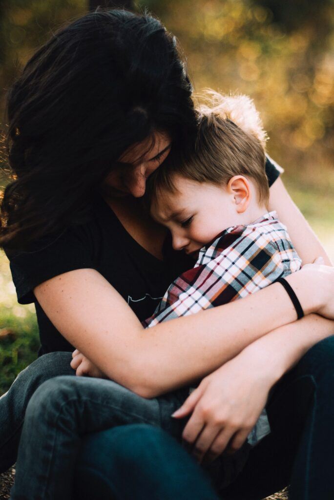 mother holding boy on her lap who is visibly upset