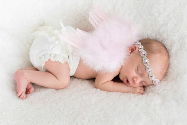 newborn baby sleeping wearing pink angel wings