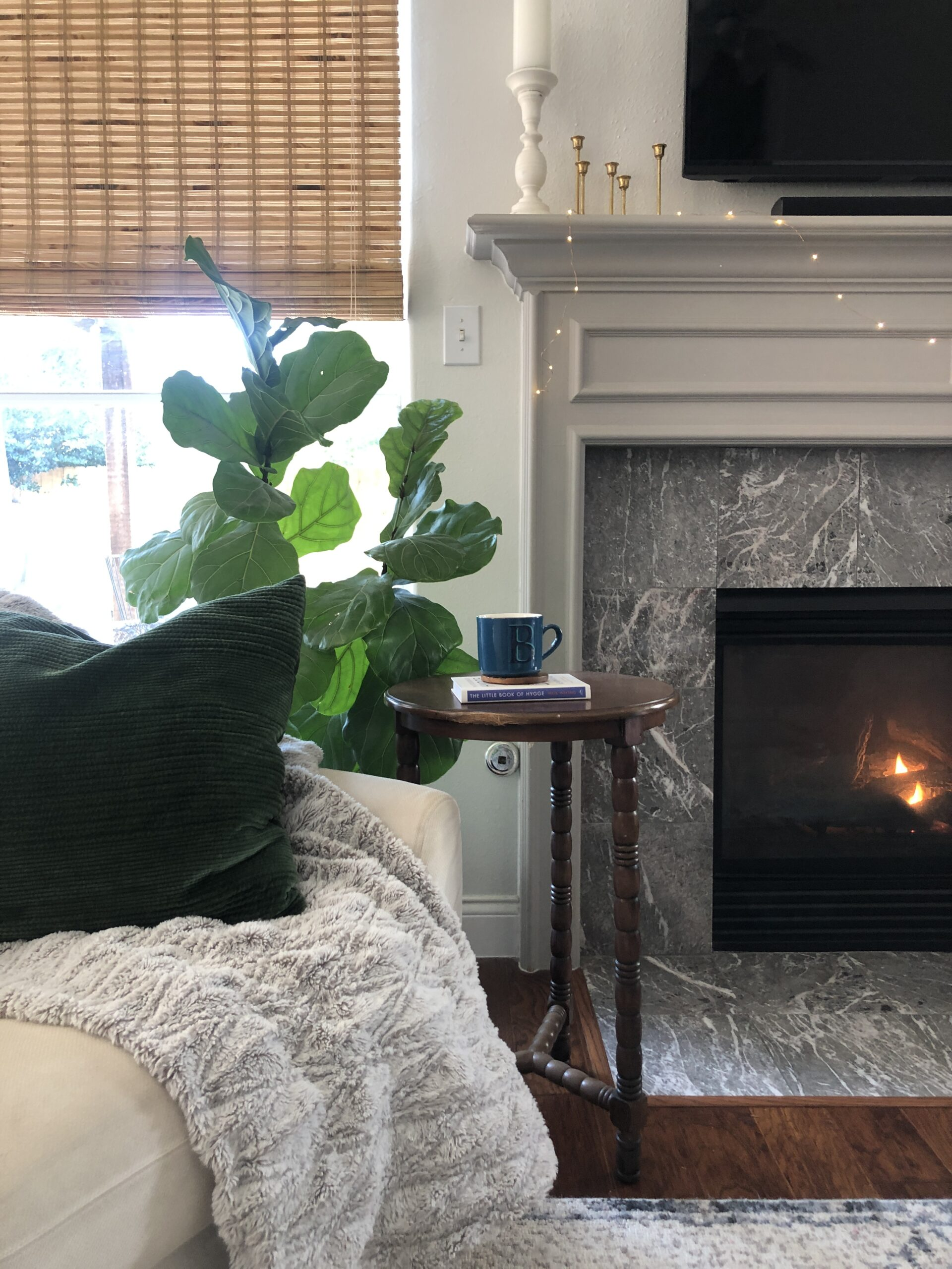 cozy hygge living room with fireplace, soft blanket, and cup of tea