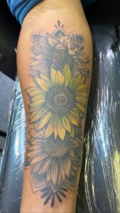 woman's arm with a sunflower tattoo