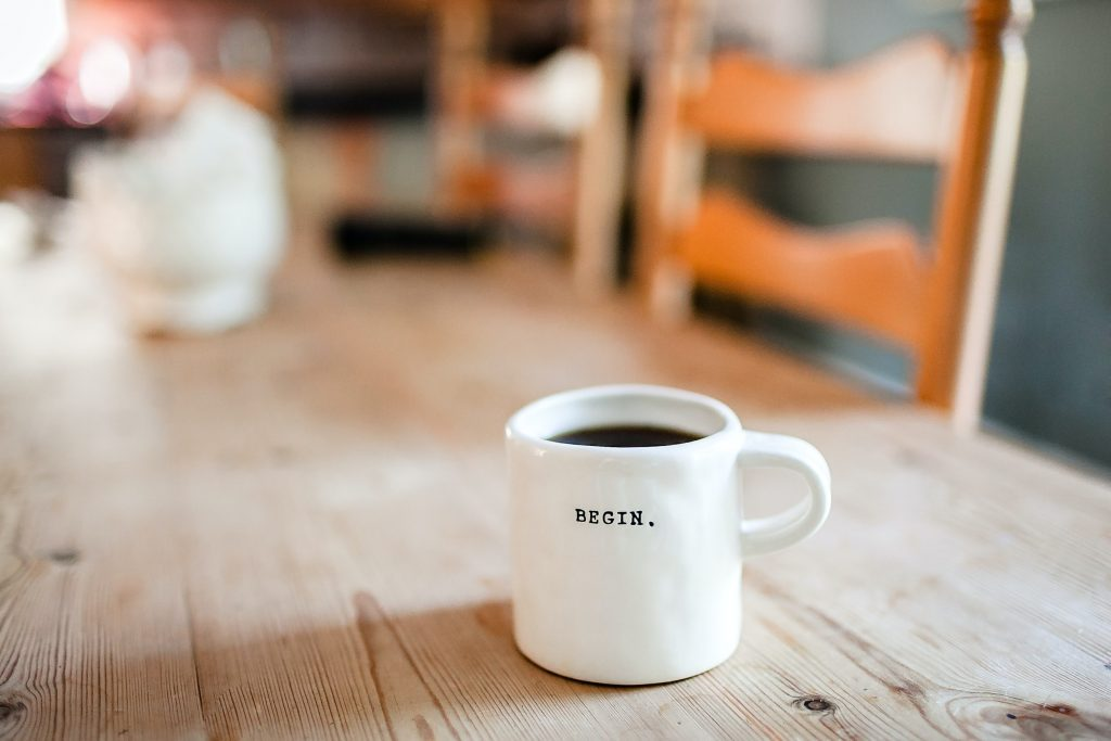 """wooden table with a coffee cup that says """"Begin"""""""