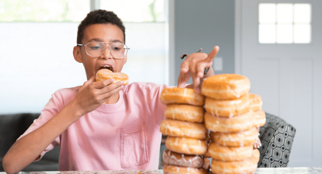 young boy holds a donut while looking at a plate stacked with donuts